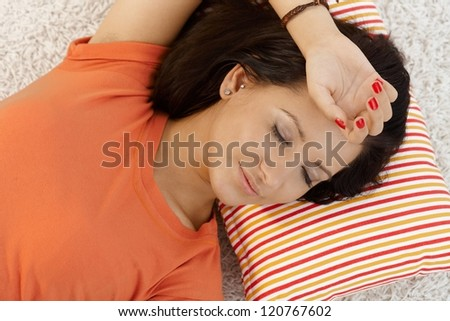 Young girl resting at home on pillow eyes closed.