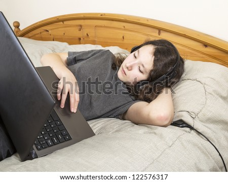 Young girl resting in bed while browsing the internet on her laptop computer