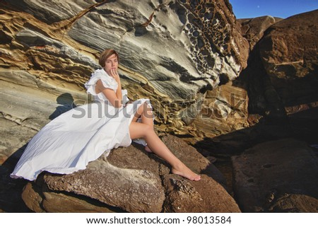young girl resting on a rocky seashore on a windy day