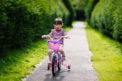 young girl ridding bicycle in the  summer garden morning