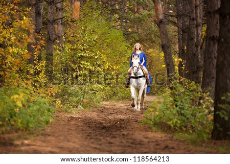 Young girl riding a white horse in the autumn park