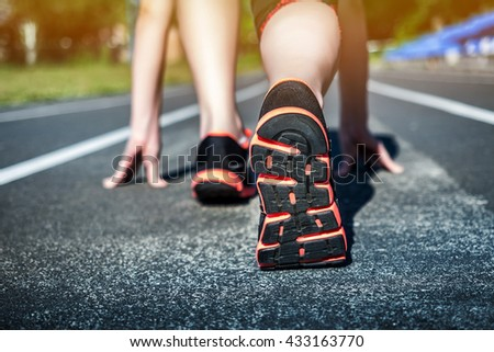 Young Girl Runner feet on track closeup focus on sport shoe. Getting ready to start