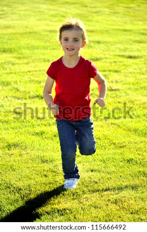 Young girl running on grass during bright summer day