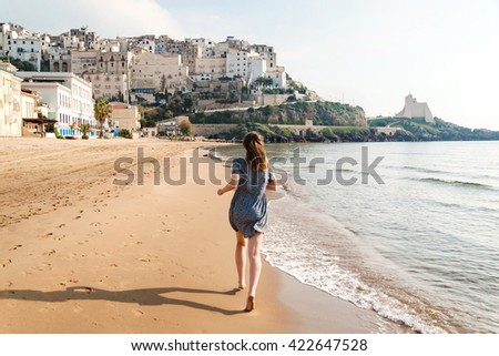 Young girl running on the beach of Sperlonga, Italy