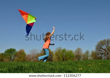 Young girl running with colorful kite against a blue sky