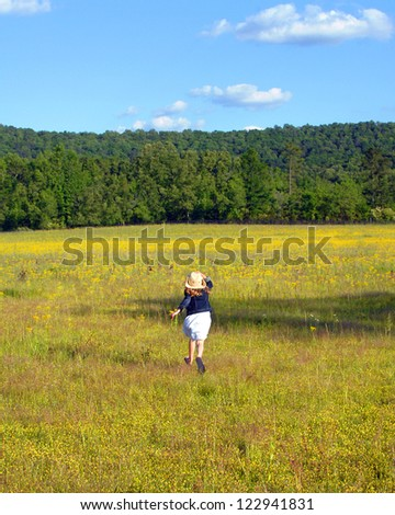 Young girl runs across a field of yellow flowers in rural Alabama.  She is holding her cowboy hat and enjoying nature.