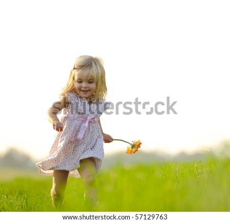 Young girl runs through a field, happy and having fun.