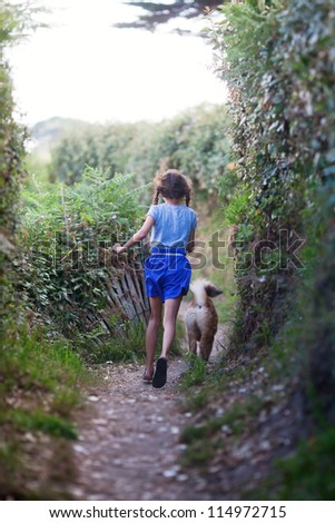 young girl runs with a young dog along a coastal path