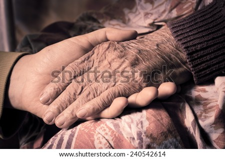 Young girl\'s hand touches and holds an old woman\'s wrinkled hand