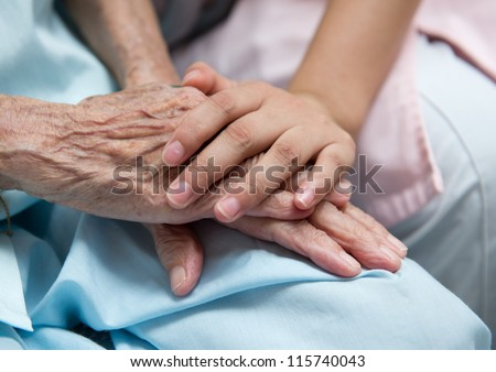 Young girl\'s hand touches and holds an old woman\'s wrinkled hands.