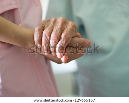 Young girl's hand touches and holds an old woman's wrinkled hands.