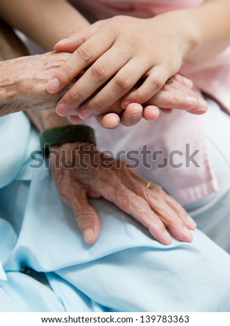 Young girl's hand touches and holds an old woman's wrinkled hands. #139783363