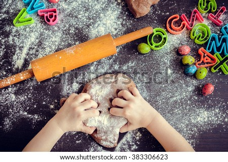 Young girl\'s hands kneading dough. Easter baking preparation. Close-up of child\'s hands baking cookies. Easter eggs. Easter food concept. Top view.