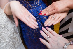 Young girl's hands, touching fingers, bride's hands with white gold diamond engagement ring and wedding ring on the finger, tanned skin, different color nails, cream and blue dresses on the background