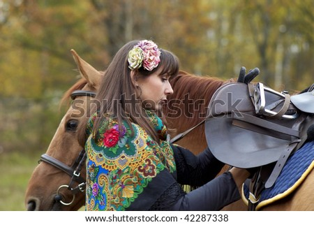 Young girl saddling her horse