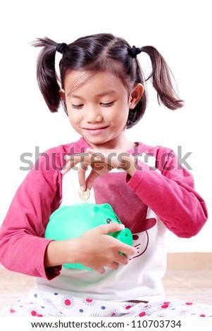 Young girl saving a coin in a piggy bank. - stock photo