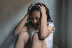 Young girl screaming in fear, Depressed teenager sitting holding head in hands,