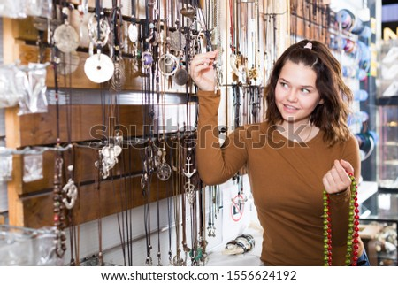 Young girl seller offering colored necklaces and pendants in the store #1556624192