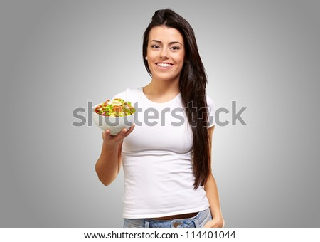 Young Girl Showing A Bowl Of Salad Isolated On gray Background