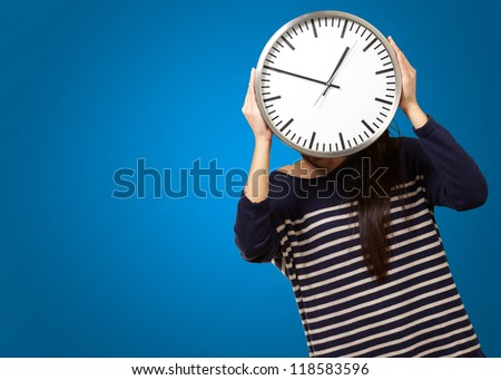 Young Girl Showing Clock And Hiding Her Face On Blue Background