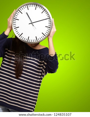 Young Girl Showing Clock And Hiding Her Face On Green Background