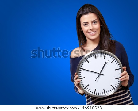 Young Girl Showing Clock On Blue Background