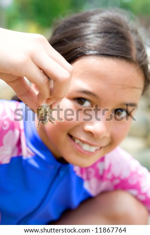 Young girl showing her little hermit crab she picked from the shore