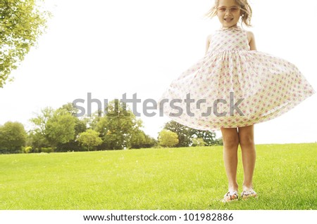 Young girl showing off her dress and wearing pink shades in the park.
