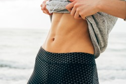 Young girl showing sporty belly against the sea on the beach