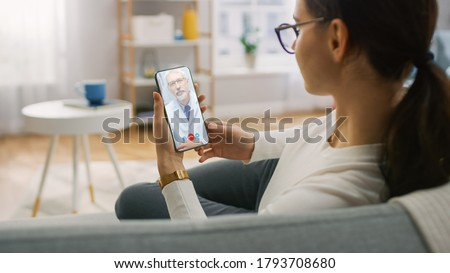 Young Girl Sick at Home Using Smartphone to Talk to Her Doctor via Video Conference Medical App. Woman Checks Possible Symptoms with Professional Physician, Using Online Video Chat Application