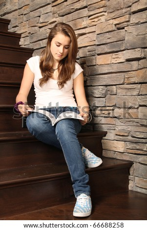 Young girl sit in stairs and reading a magazine