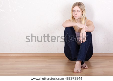 Young girl sits on the floor with her back pressed against the wall.