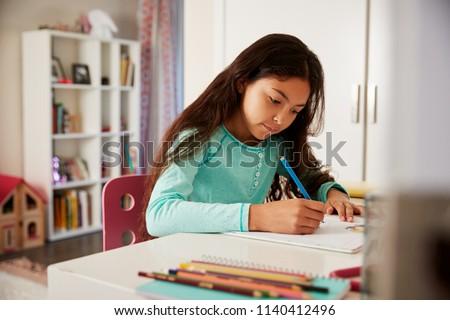 Young Girl Sitting At Desk In Bedroom Doing Homework
