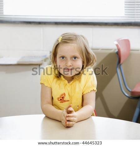 Young girl sitting at table in school classroom. Square format. - stock photo