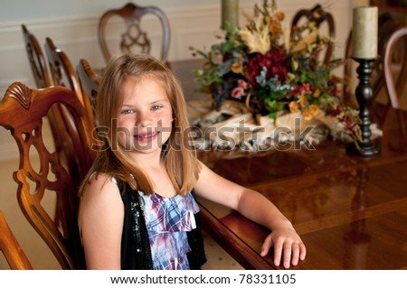 Young girl sitting at wood finished dining room table with decorations