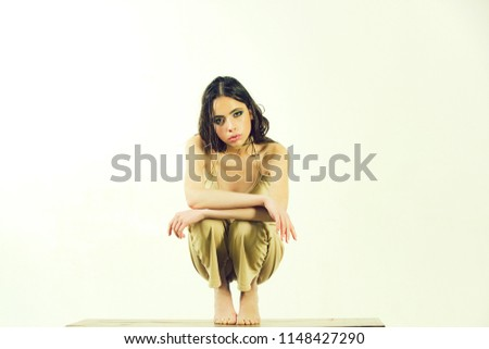 young girl sitting barefoot with fashionable makeup and long brunette wet hair in beige underwear on slim body isolated on white background #1148427290