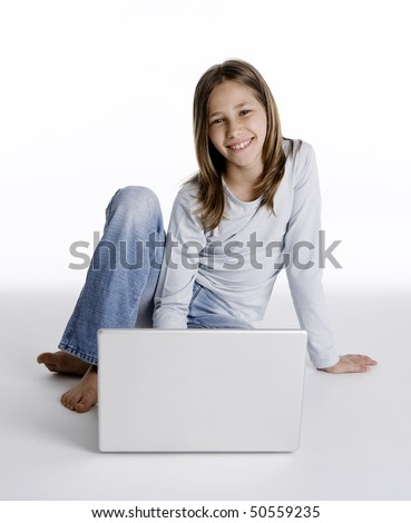 Young girl sitting down  on the floor with laptop computer, studio shot isolated on white background - stock photo