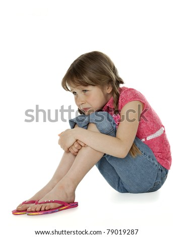 Young girl sitting, hugging knees, sad facial expression, on white.