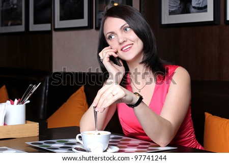 Young girl sitting in a cafe for a cup of tea and talking on the phone
