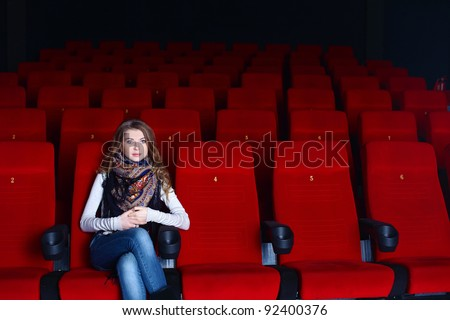 Young girl sitting in cinema and watching movie