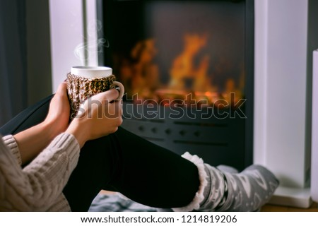 Young girl sitting in front of the fireplace and holding cup of tea in hand on legs and warming. Woman in winter clothes and wool socks. Winter and cold weather concept. Close up, selective focus