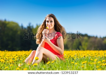 Young girl sitting in spring on a flower meadow with dandelion