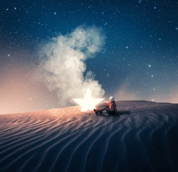 Young girl sitting next to a fallen star in the desert.
