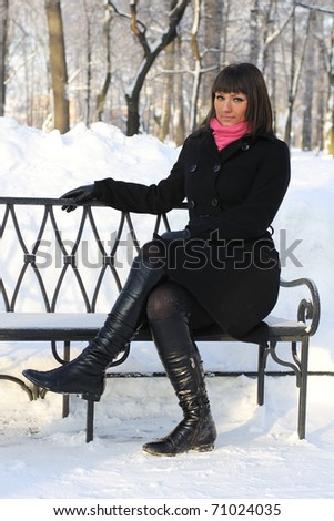 Young girl sitting on a bench in the park, winter, snow