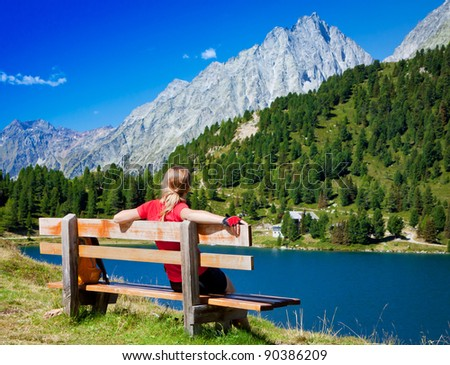Young girl sitting on a bench near the lake in the mountain