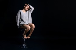 young girl sitting on a high chair against a dark background, studio photo with copy space