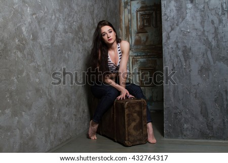 Young girl sitting on a huge old suitcase #432764317