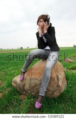 young girl sitting on a rock