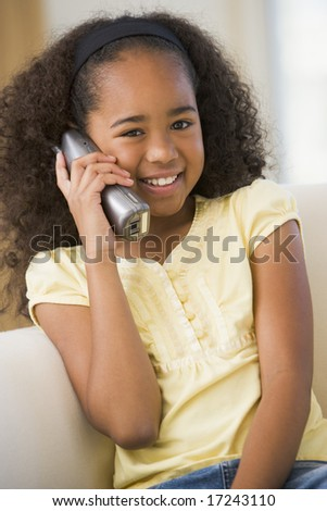 Young Girl Sitting On A Sofa, Talking On A Telephone