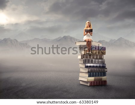 Young girl sitting on a stack of books and reading